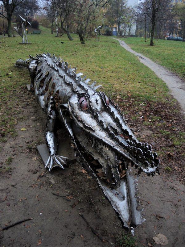 """Zdjęcie w formacie pionowym przedstawiające aligatora przodem w prawo skos do patrzącego. Z prawej przebiega ścieżka, w głębi widać pozostałe rzeźby """"Łyżwiarzy"""" i """"Ptaka""""."""