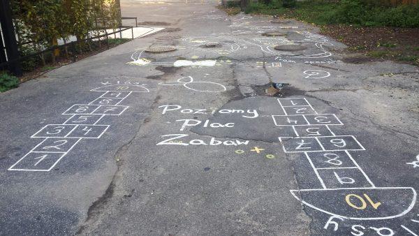 Plac zabaw widok z dwoma polami do gry w klasy na pierwszym planie. W głębi zniszczona nawierzchnia, cztery kanały i fragmenty zaniedbanego zieleńca po prawej oraz Zielonej Sali wykładowej po lewej. Napis Poziomy Plac Zabaw po środku.